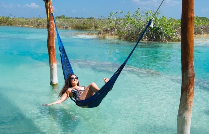 Kate relaxes in a hammock on top of bright clear turquoise water in Bacalar, Mexico, running her hand through the water.