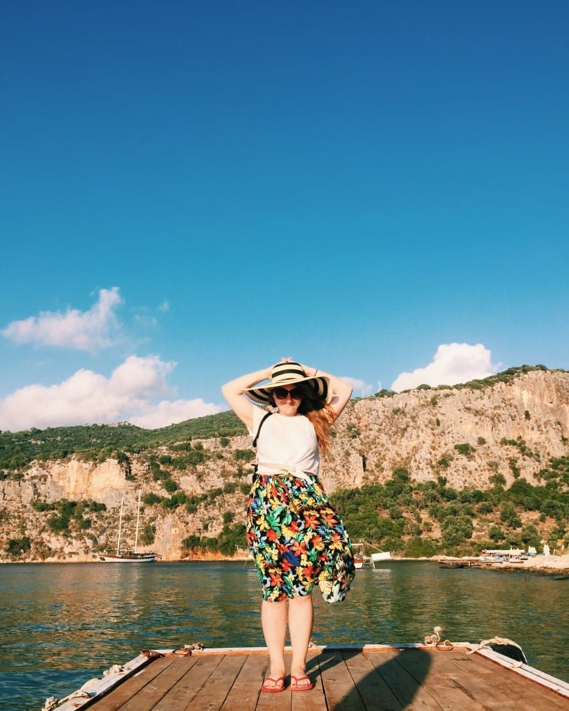 Katie in a patterned skirt, white top, and floppy hat smiling in front of the dark green Mediterranean near Kas.