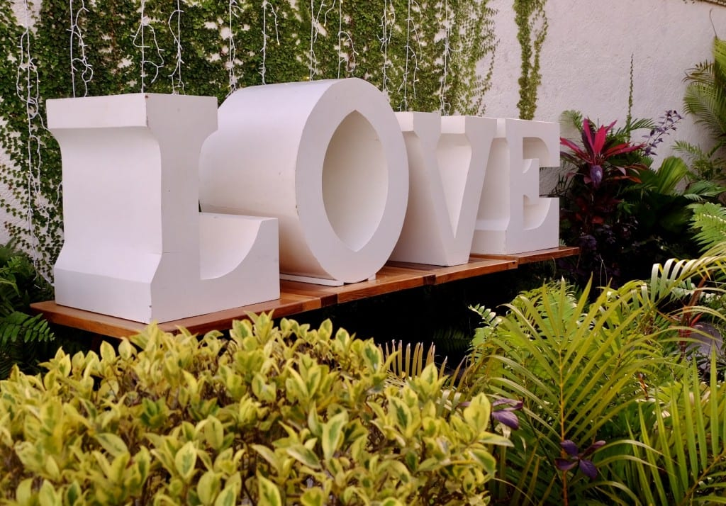 Giant white letters reading LOVE surrounded by greenery in Bacalar.