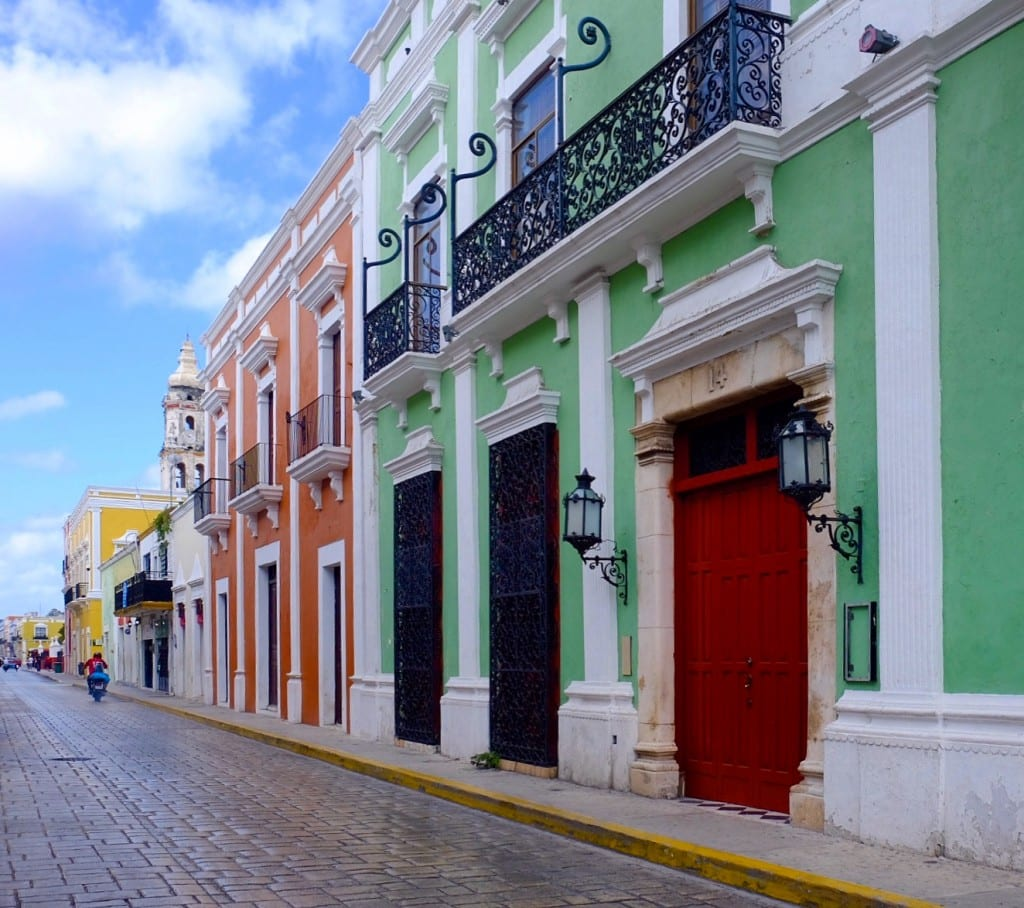 Campeche's bright green, orange, and yellow buildings, all over stately with white trim.