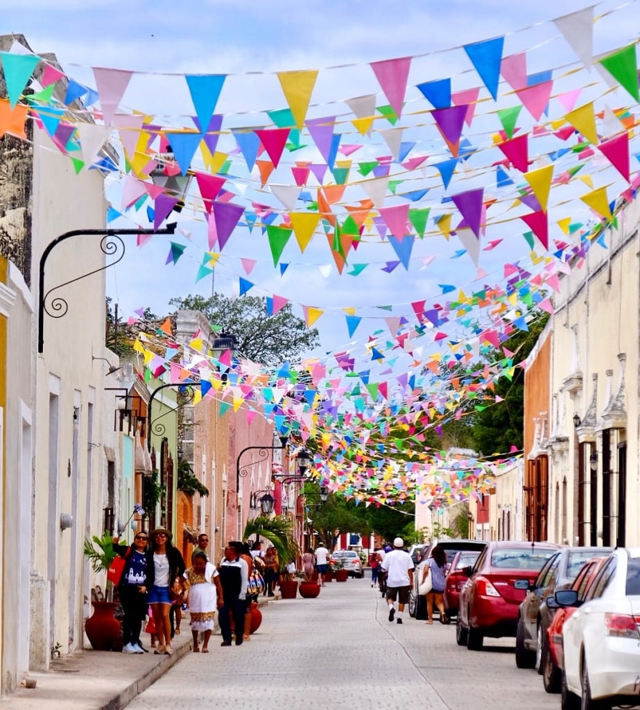 A Valladolid street covered with hundreds of brightly colored flags.