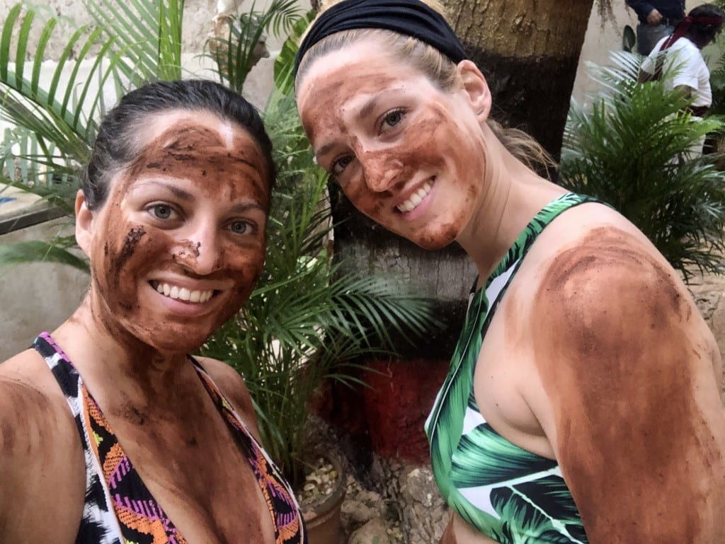 Kate and Sarah covered in dark brown mud for the Mayan healing ceremony.
