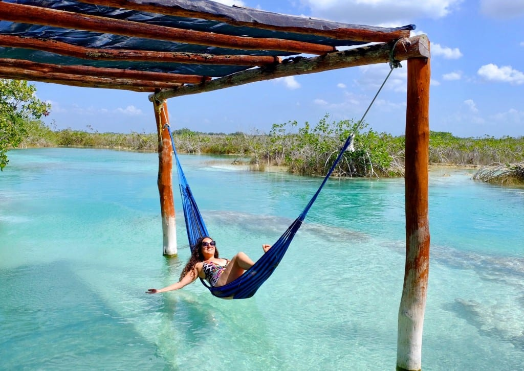 Kate lying in a hammock in bright turquoise water in Bacalar.