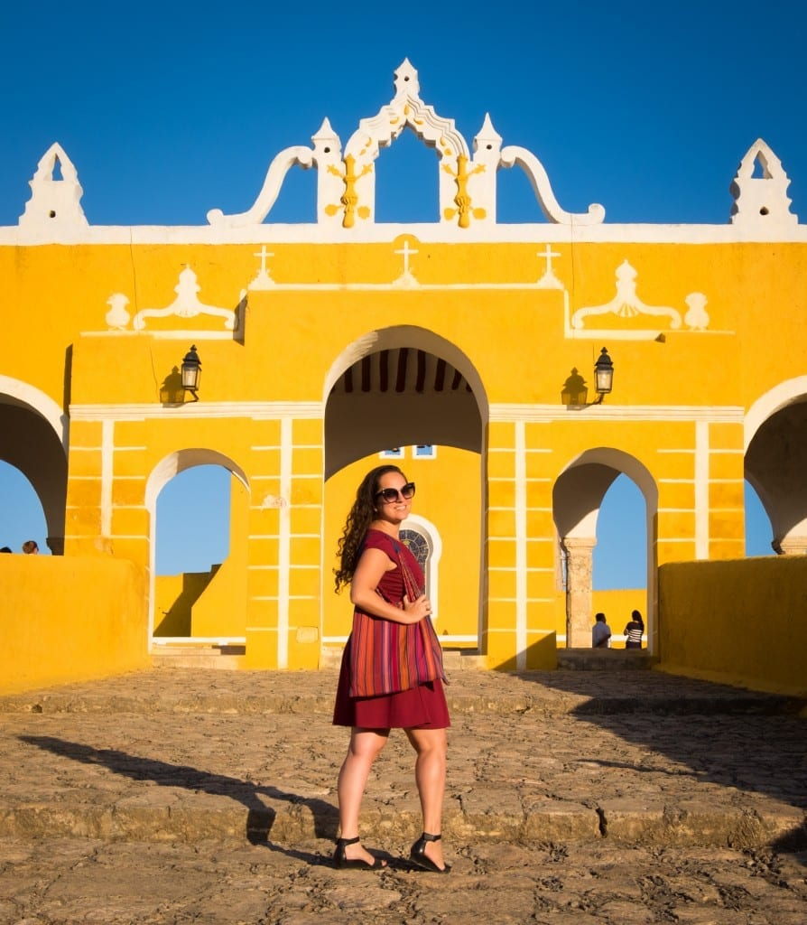 Kate stands in front of a yellow monument in Izamal.