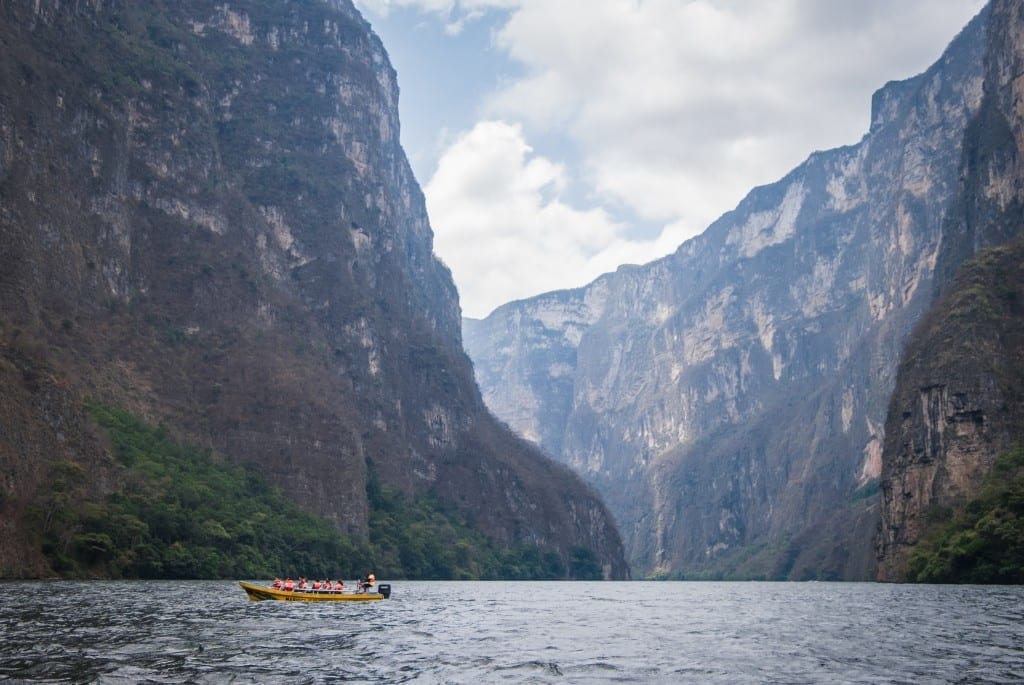 A yellow boat in Sumidero Canyon, surrounded by mountains.