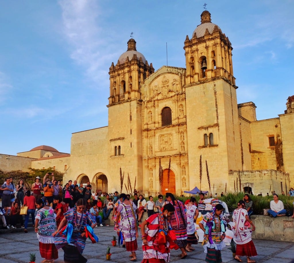 Dancers in indigenous clothing in front of a church in Oaxaca.