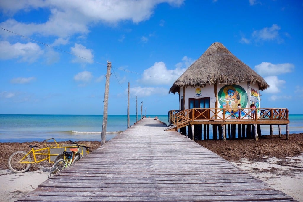 A dock leading out into the blue water in Holbox, Mexico.