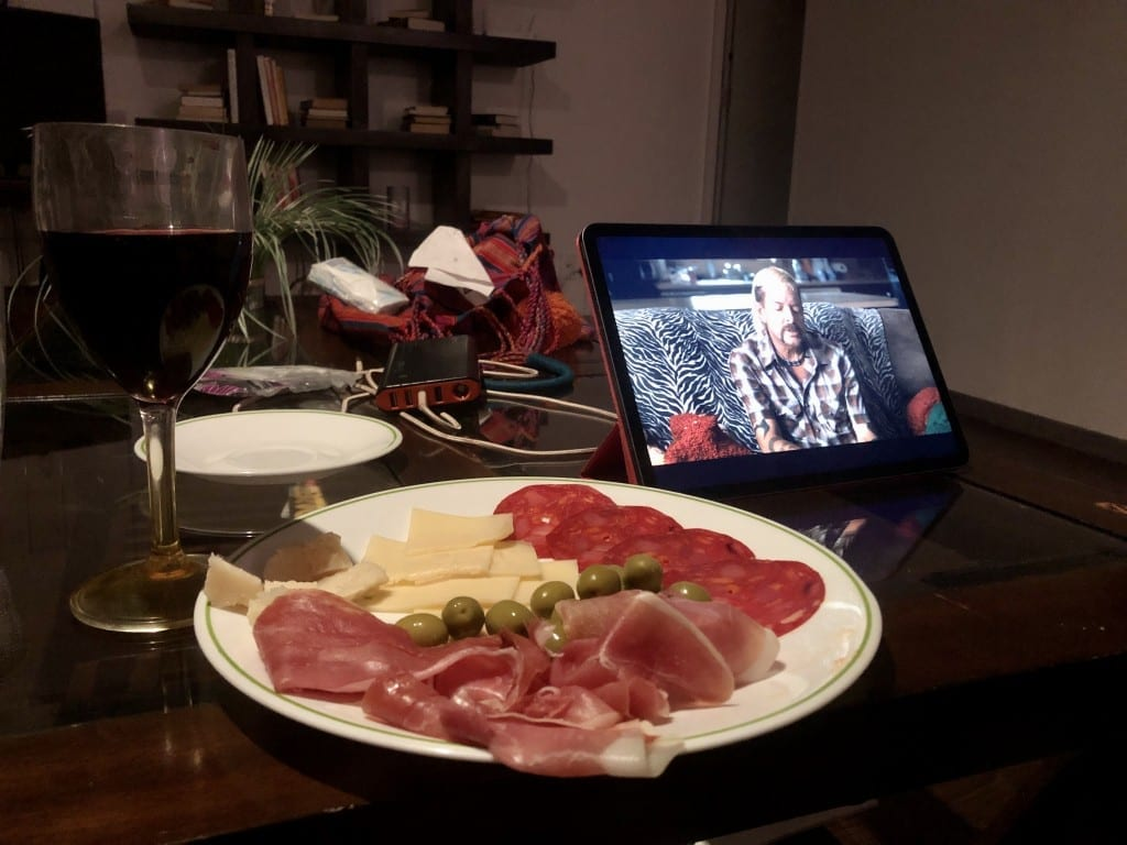A plate of cured meats and cheeses in front of an iPad with Joe Exotic on it
