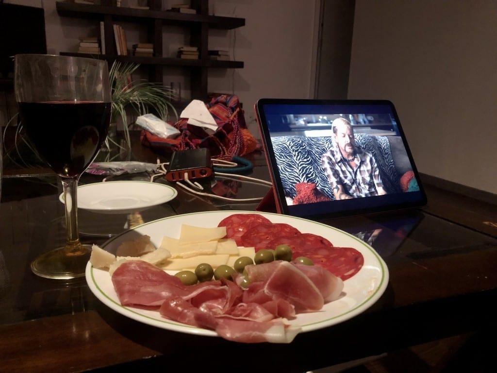 Une assiette de charcuteries et fromages devant un iPad avec Joe Exotic dessus