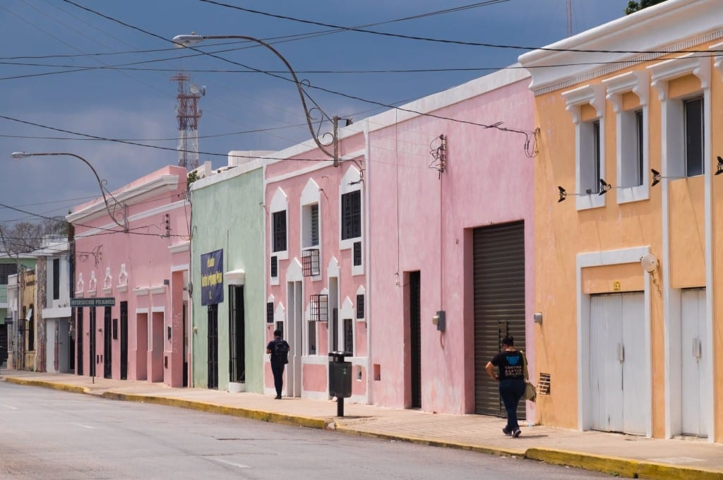 A street with pink, yellow and green homes in Merida, Mexico.