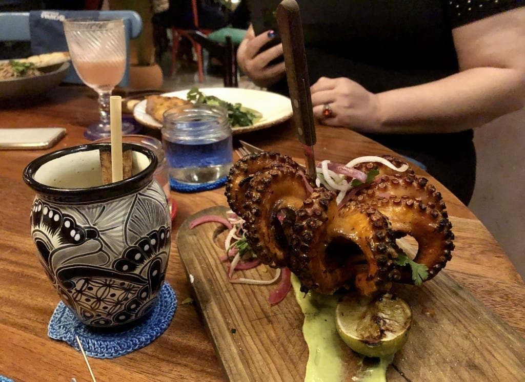 A giant octopus on a wooden plate with a fork sticking straight out of it, served next to a cocktail at Micaela.