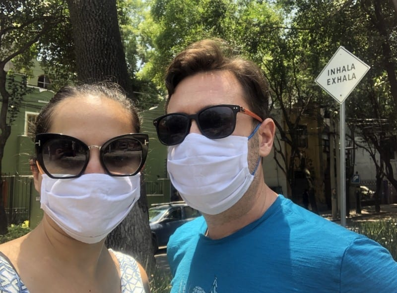 "Kate and Charlie wearing face masks and sunglasses in front of a sign that reads ""Inhala Exhala"" in Mexico City."