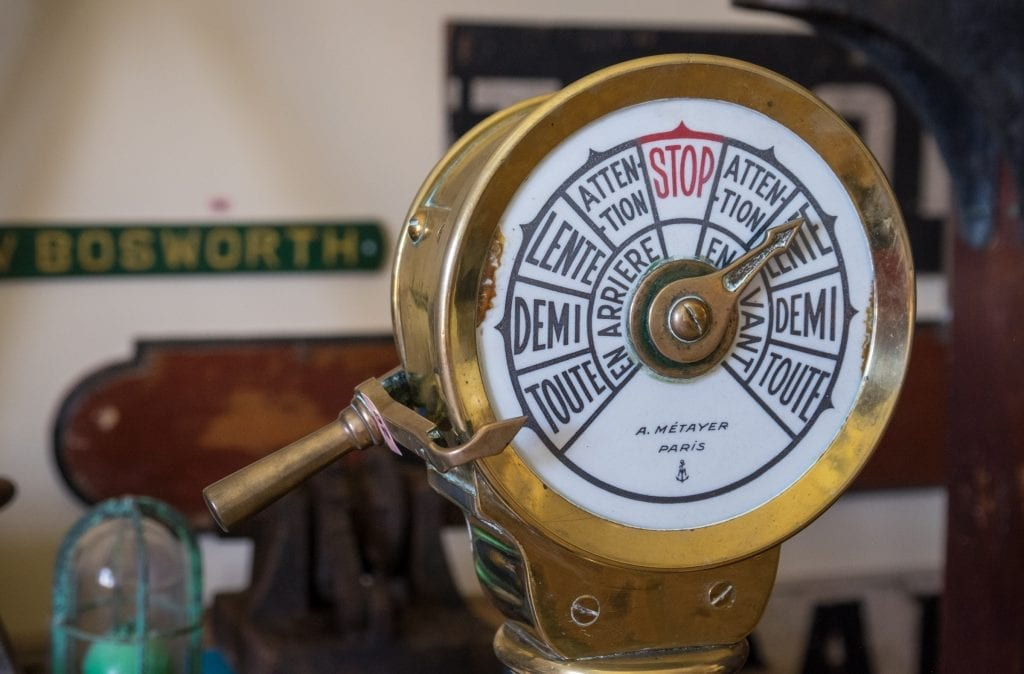 "A vintage ship navigation tool reading ""Toute, Demi, Lente, Attention and STOP!"""