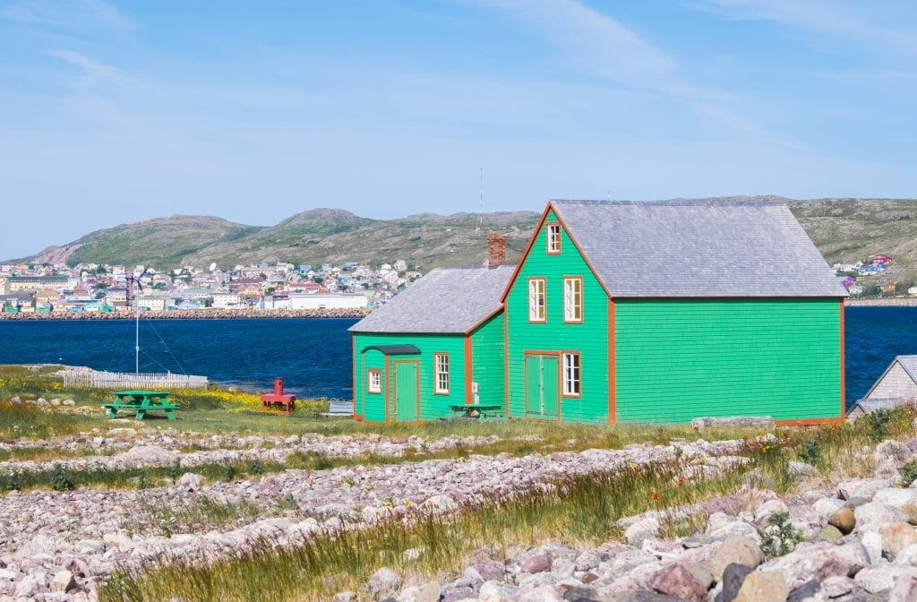 A bright green cottage with orange trim on the edge of the ocean, St. Pierre tow in the background.