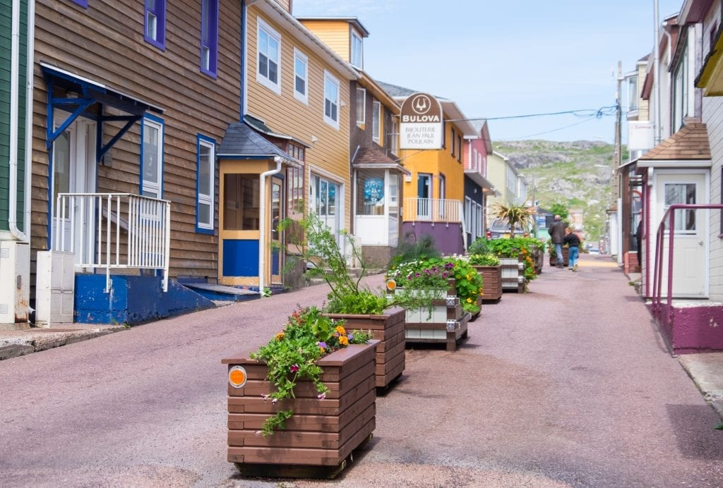 Colorful homes in St. Pierre and a street filled with flower planters.