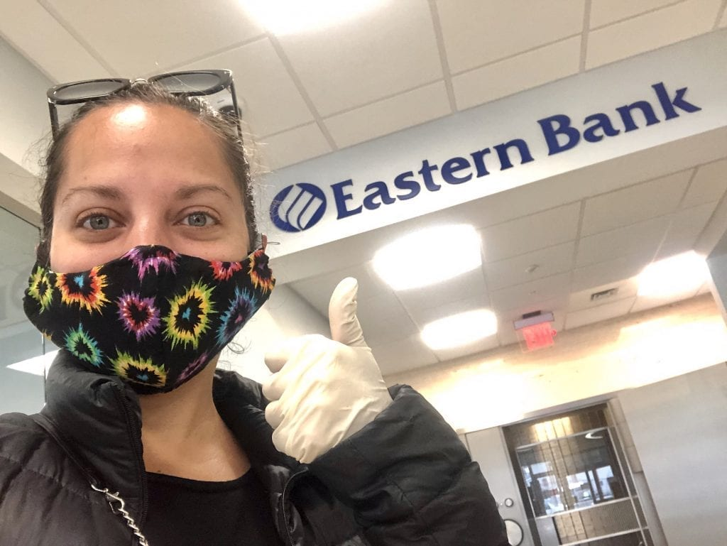 "Kate poses with a mask on by an ""Eastern Bank"" sign, giving the thumbs up with a rubber gloved hand."