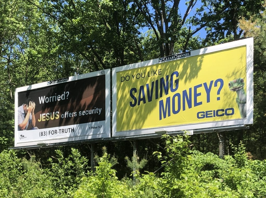 "Two billboard ads: one says ""Worried? Jesus offers security."" Other says ""Do you like saving money? GEICO."""