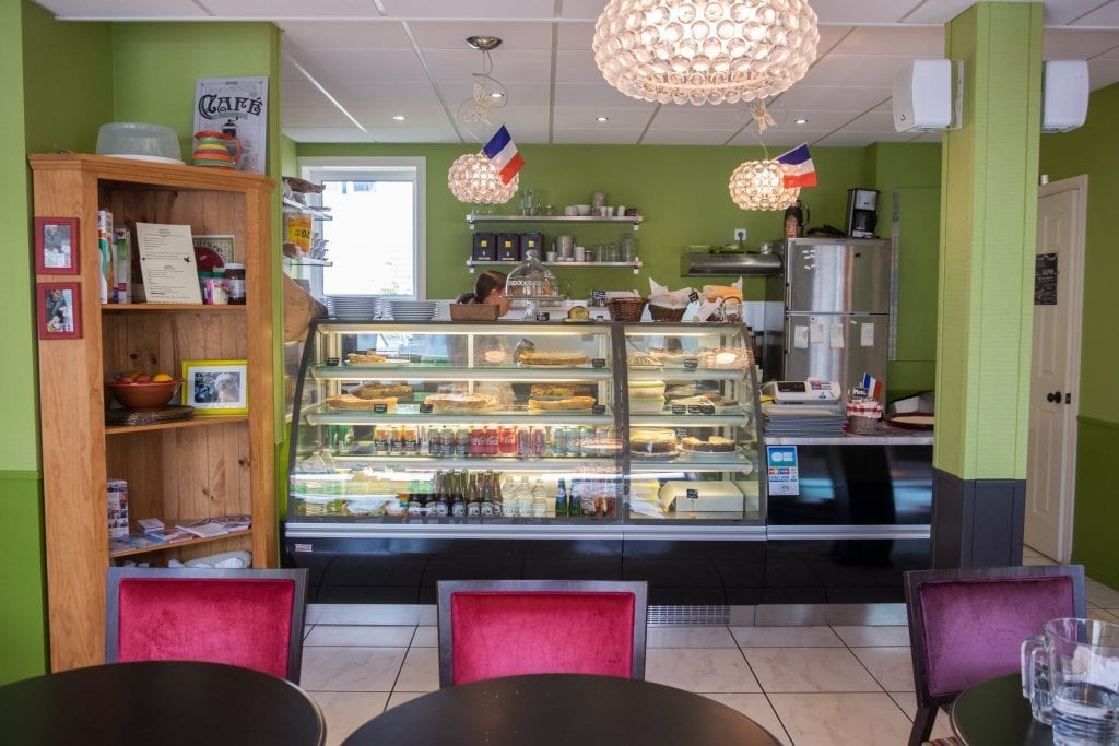 A cafe with pastries and sodas in the glass case and French flags hanging from the ceiling.
