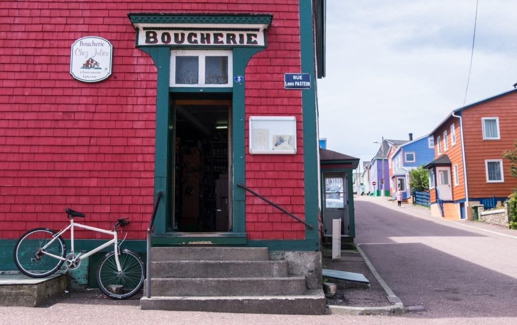 "A red shingled house with a doorway reading ""Boucherie"" and a white bicycle parked next to it."