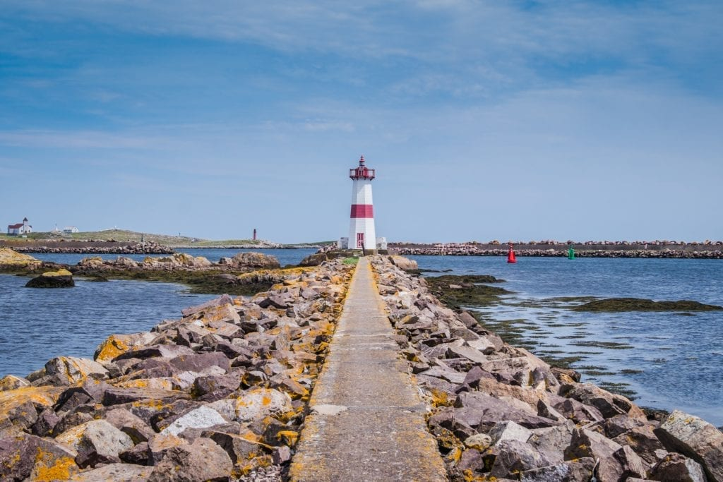 A rocky path leading to a red and white lighthouse.