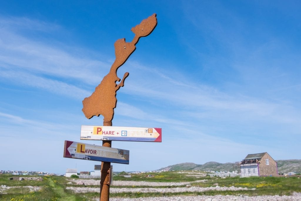 "An island-shaped sign against a blue sky with signs pointing to ""Phare"" and ""Lavoir."""