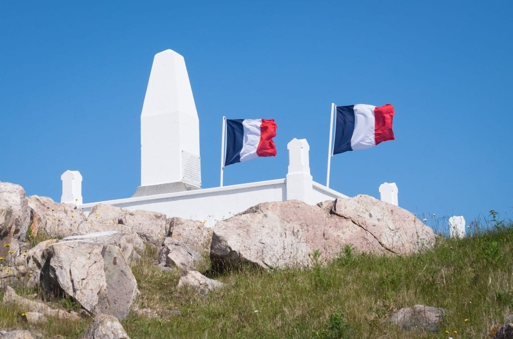 Two French flags waving on top of a white marble monument on top of a rocky hill.