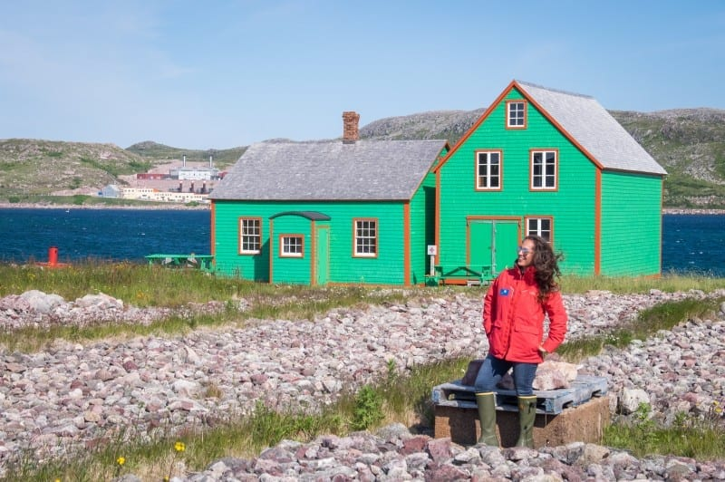 Kate wears a bright red jacket and stands in front of a green wooden cottage on the rocky shore of St. Pierre island.