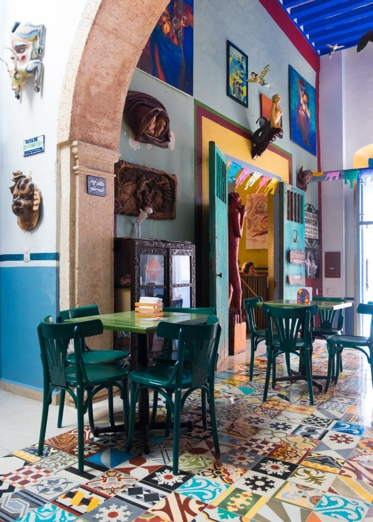 A cafe in Mexico with wild patchwork tiles on the ground.