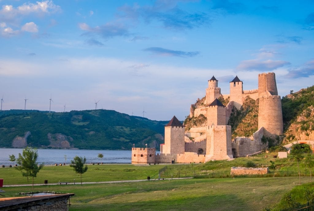 Golubac Fortress, which looks like a Harry Potter-like place with towers sticking out of a hillside in front of the Danube. The fortress is lit up orange from the sunset underneath a bright blue sky.