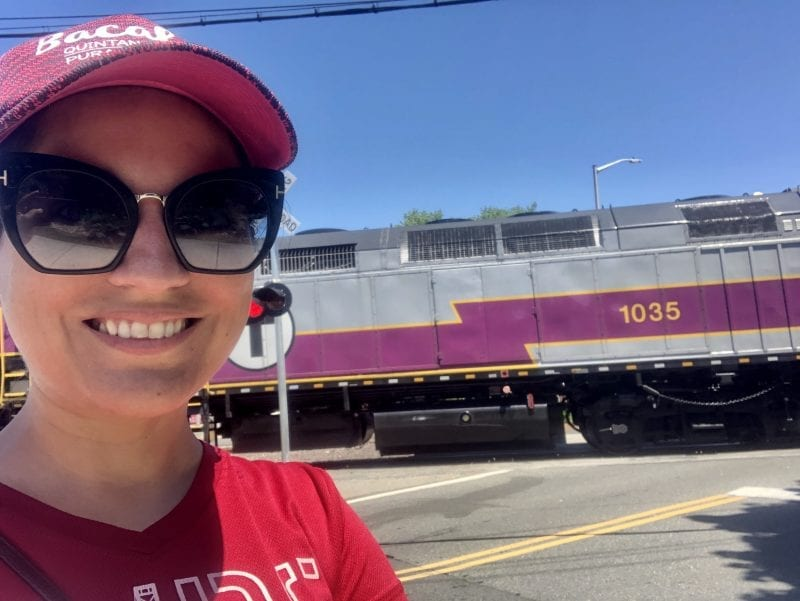 Kate takes a selfie and smiles in front of a purple and gray commuter rail train.