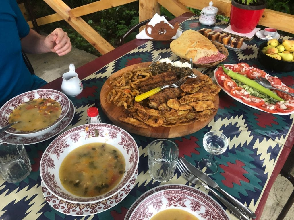 Tons of food on a patterned tablecloth, including big bowls of fish soup, fried fish and zucchini, spinach, kajmak, boiled beans, a platter of tomatoes topped with onions and cucumbers with a big green pepper on top, a loaf of bread, a bowl of small pears, four slices of plum-stuffed cake.