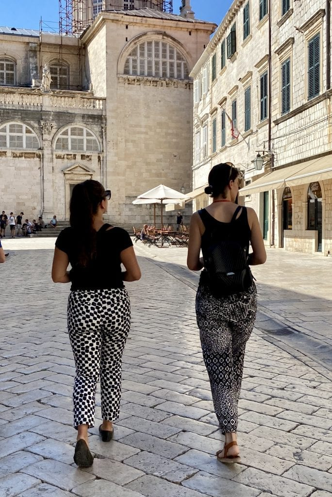 Kate and tour guide Ana walking down an empty street in the old town of Dubrovnik, facing away from the camera. Both wearing black sleeveless tops and black and white printed pants.