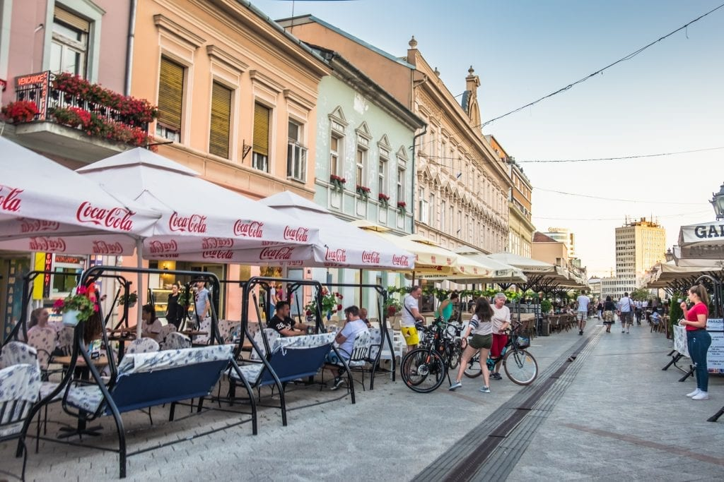 Street cafes in Novi Sad. The buildings in the background are pastel shades of pink, orange, and mint green.