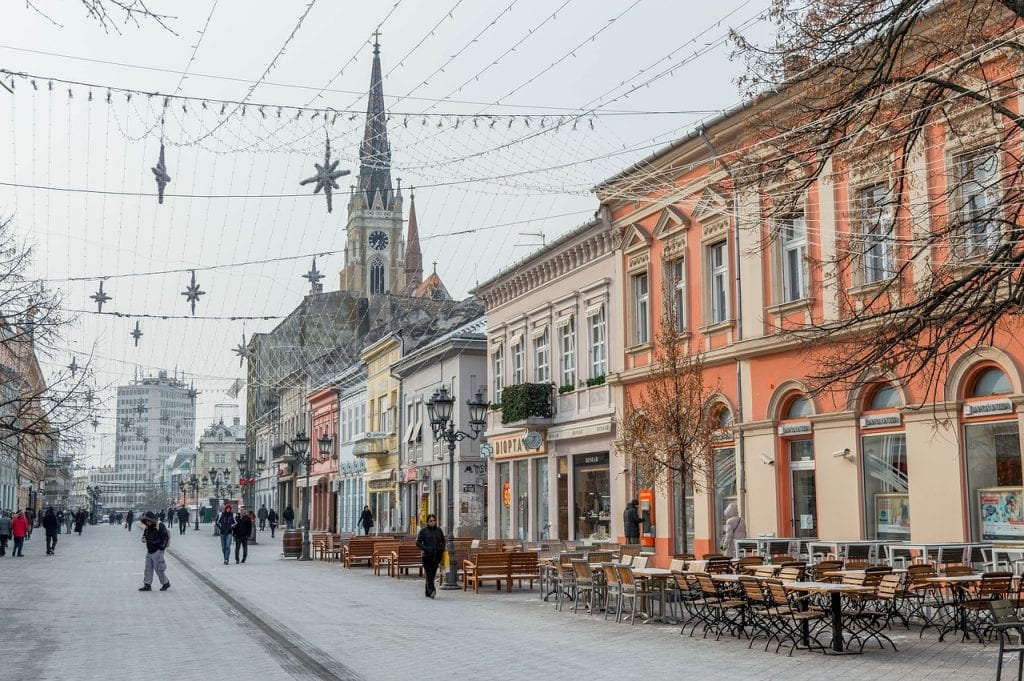 Colorful buildings and street cafes in Novi Sad, Serbia, leaving to a church.