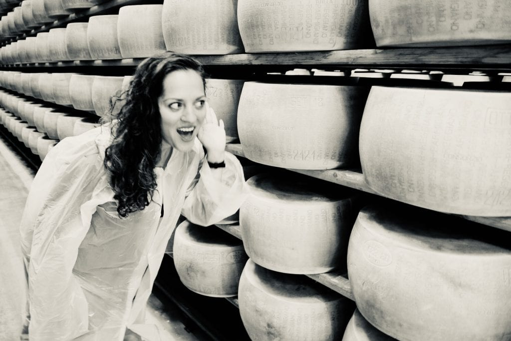 Kate stands in front of rows of parmigiano reggiano cheese wheels and holds her hand up to her ear like she's listening to them.