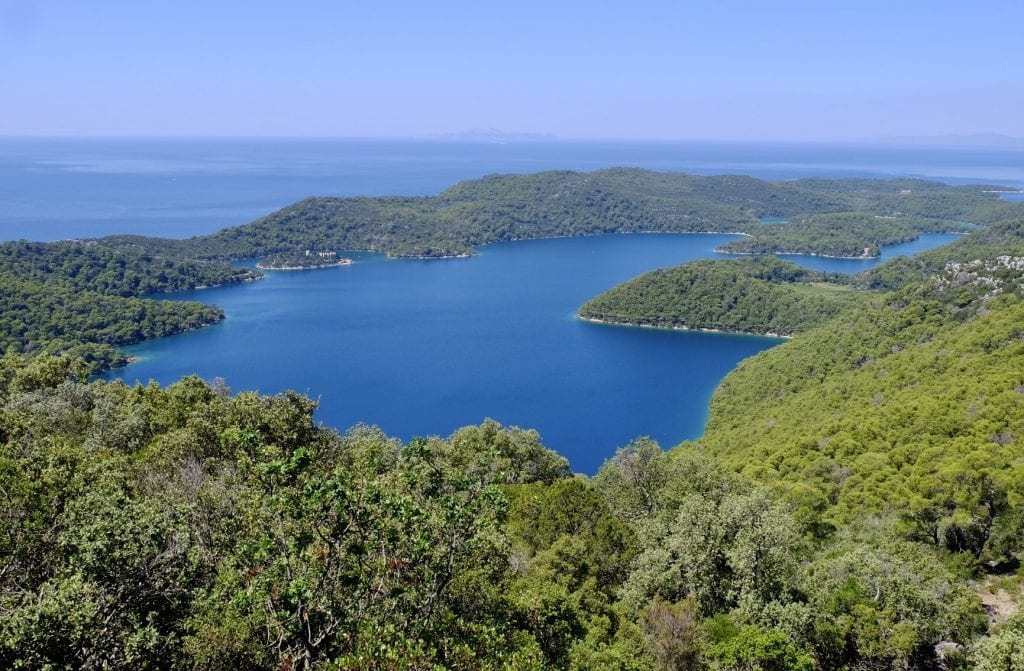 The view from above Mljet, an island covered with lush green trees, and in the center, a bright blue saltwater lake.