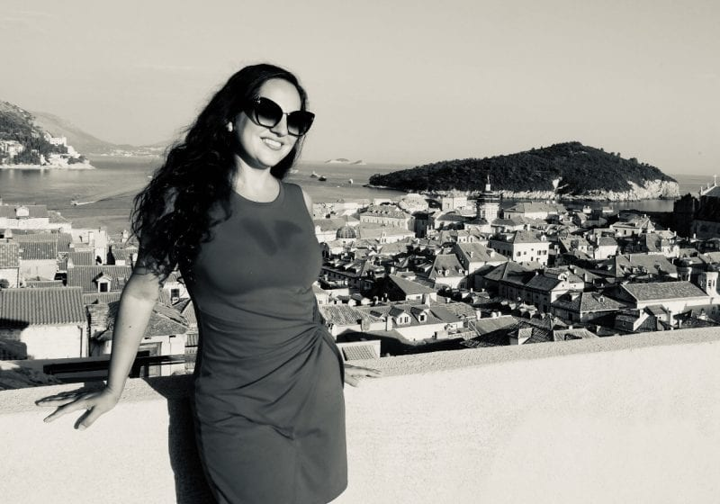 Kate stands in front of the Old City of Dubrovnik, rising behind her in terra cotta roofs and church towers, green wooded Lokrum Island in the distance.