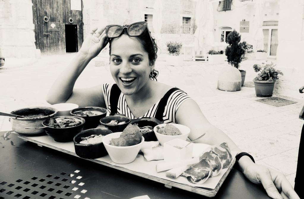Kate crouches in front of a large spread of food, each in its own small plate, in Monopoli, Italy.