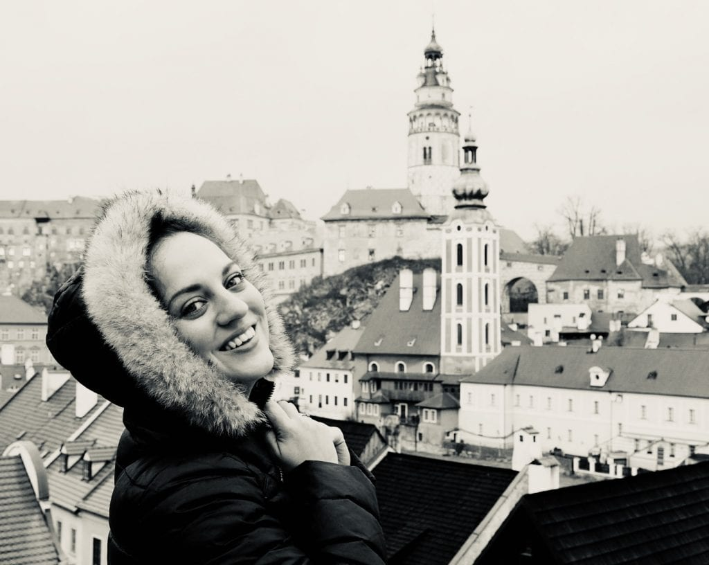 Kate wears a furry hooded coat and clasps her hands in joy in front of the church towers of Cesky Krumlov.