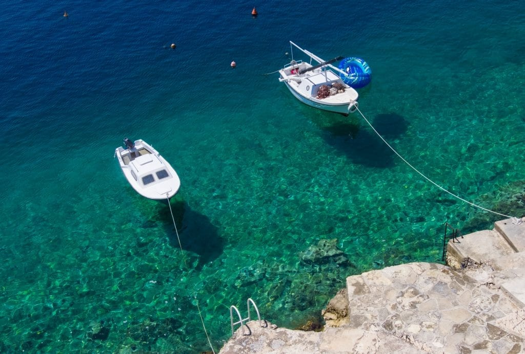 Two small white boats anchored in bright teal water leading to a rocky shoreline.