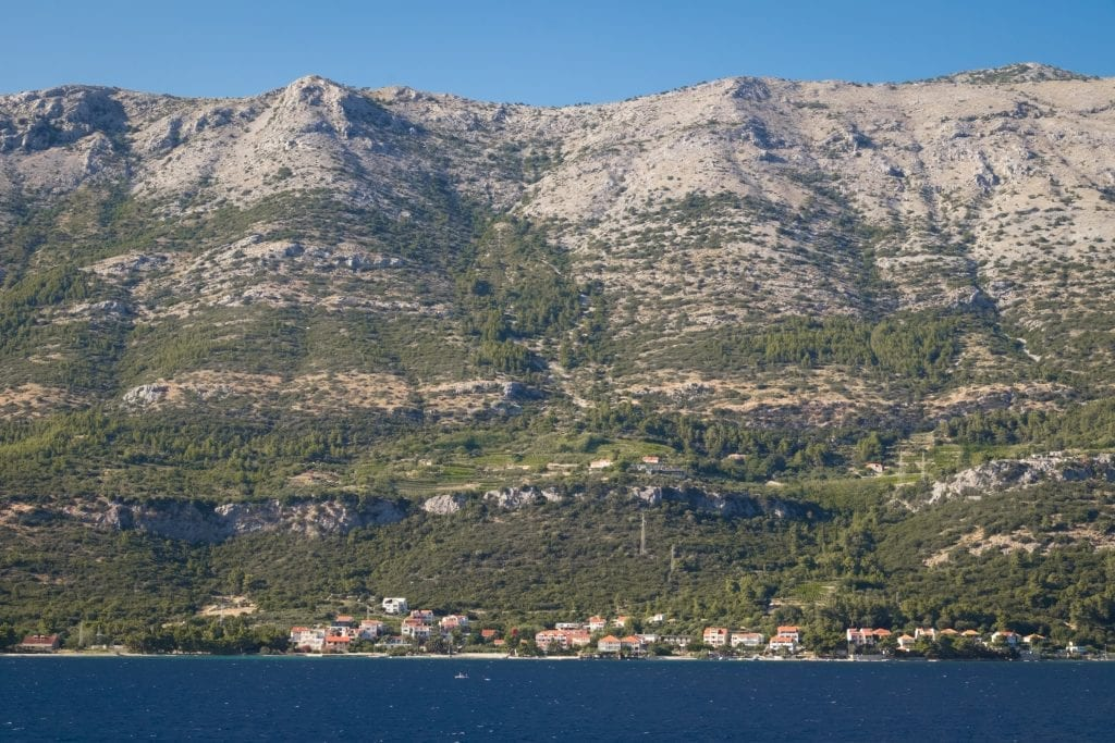 The view of Pelješac from Korčula town: a zoomed-in view of a tiny small town of white homes with orange roofs, and straight upward is a mountain, lots of greenery near the bottom, and more and more empty gray stone near the top.