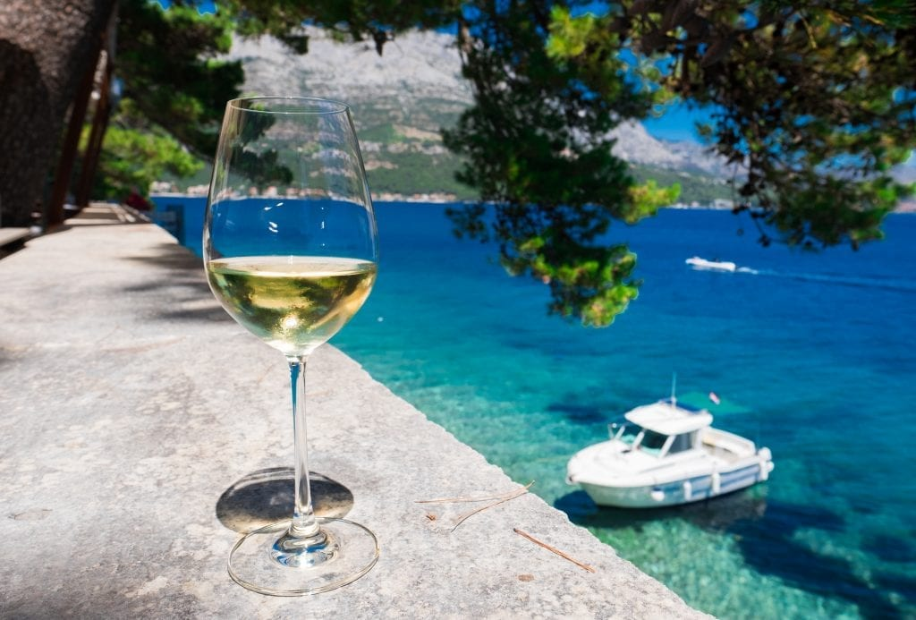 A glass of golden Grk wine in the foreground on the edge; in the background, bright blue-green water and a small boat.