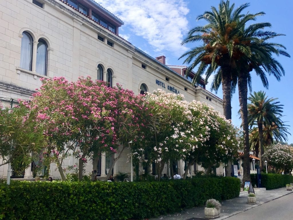Hotel Korcula de la Ville, a white stone building with several small trees in front, blooming in pink and white.