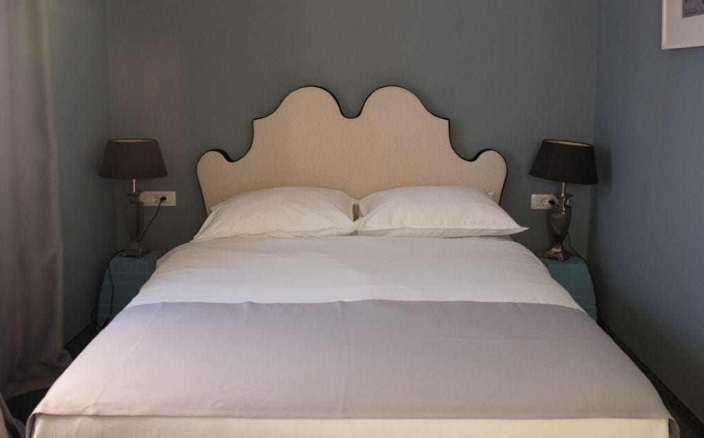 A white bed with a curvy white fabric headboard in the hotel, small tables with black lamps on each side.