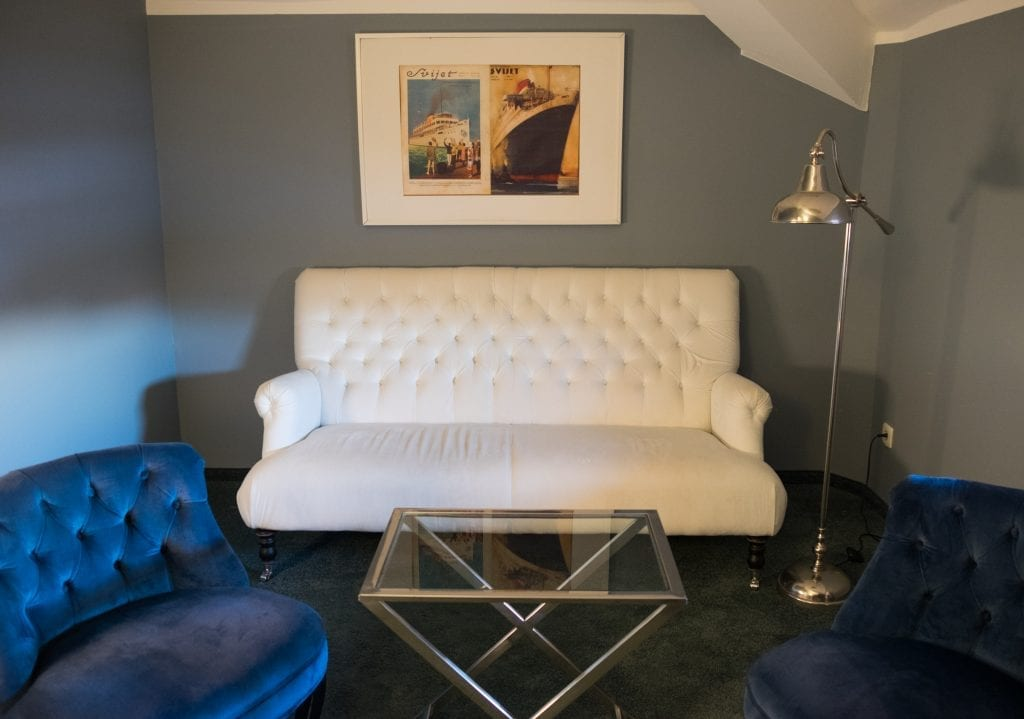 A white loveseat and framed photo of steamships above it; two navy blue chairs on each side.