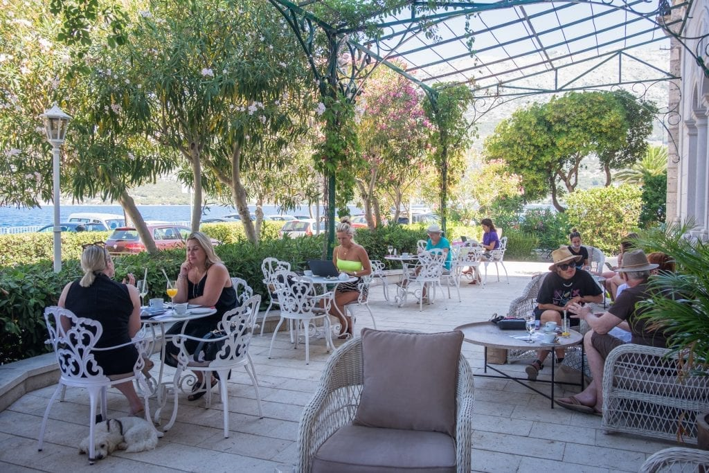 An outdoor terrace filled with several white wrought-iron tables, some of them with people sitting at them enjoying drinks or working on laptops.