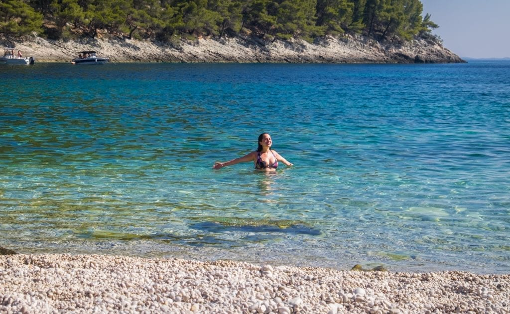 Kate swimming in the clear blue-green water at Pupnatska Luka, holding her arms outward and smiling, looking at the sky (actually I was just trying to make sure the light hit my face right).