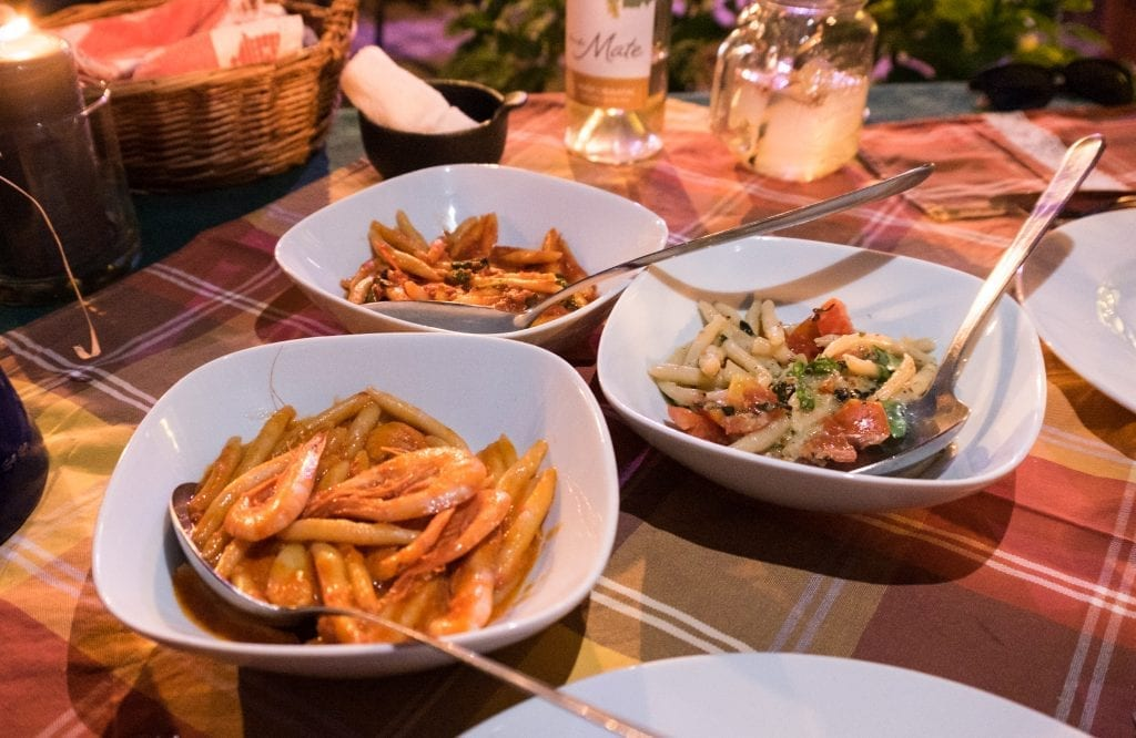 Three plates of oblong hand-rolled pasta: one with shrimp, one in tomato sauce, one in almond pesto with cherry tomatoes.