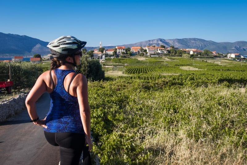 Kate wears a racerback top and bike helmet and stands with her hand on her hip, overlooking the vineyards of Lumbarda, Croatia.