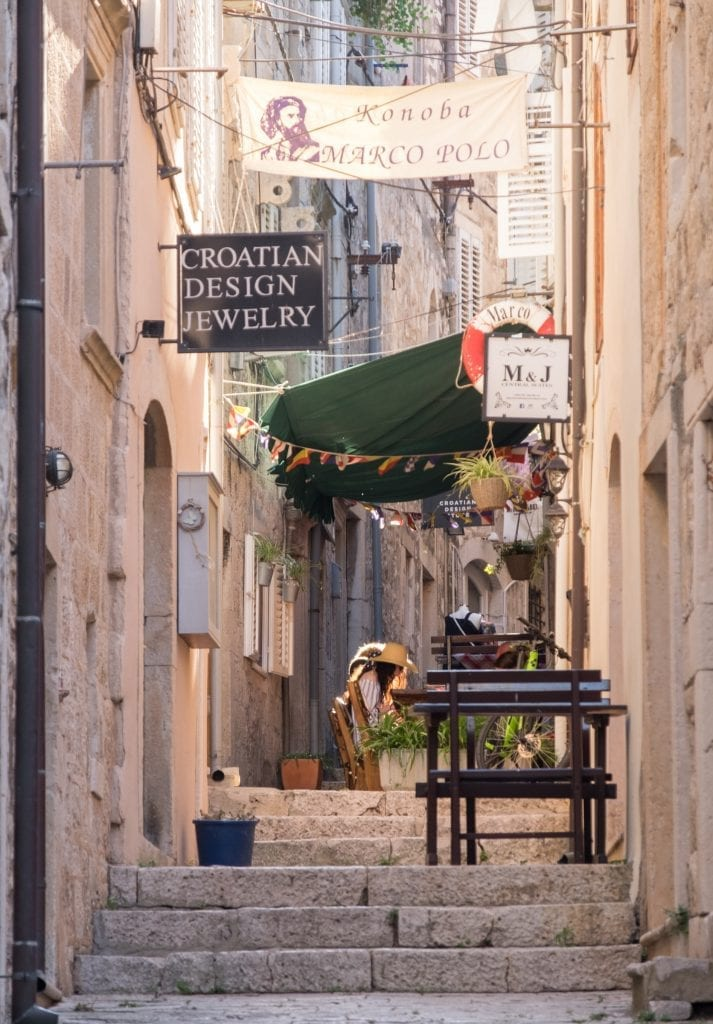 A narrow alley filled with stairs, and some tables for dining.